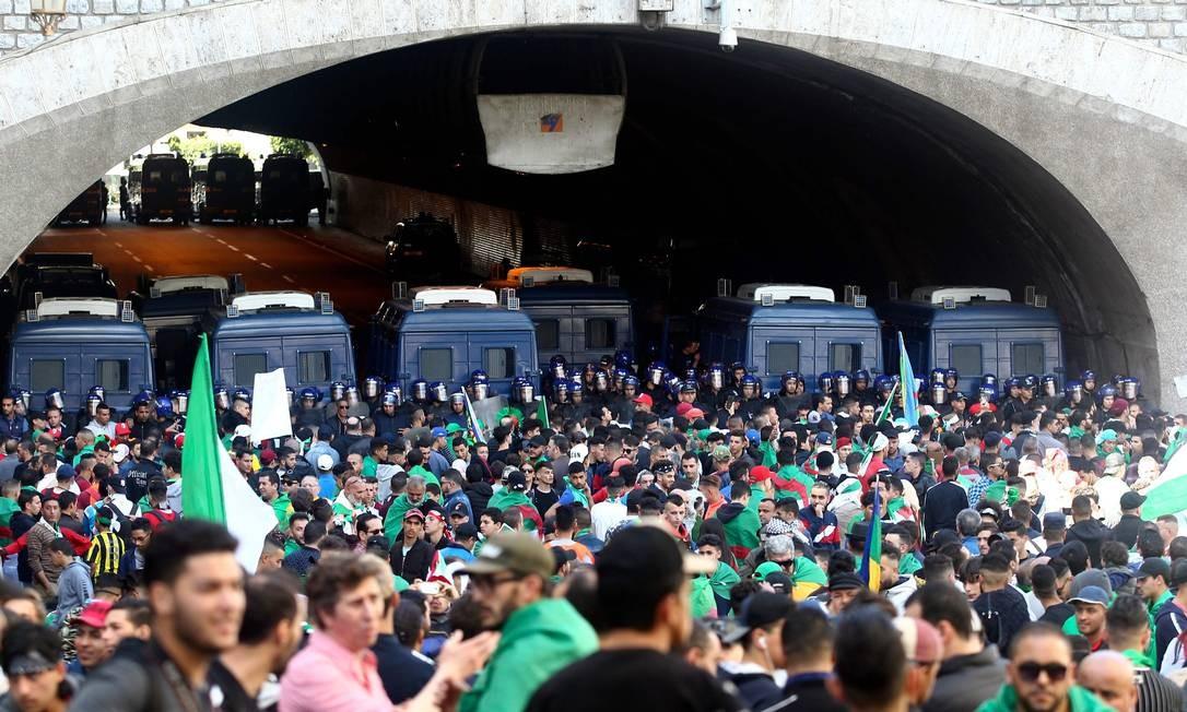 Polícia argelina monta guarda enquanto manifestantes se reúnem durante uma manifestação contra o governo na capital, Argel Foto: - / AFP