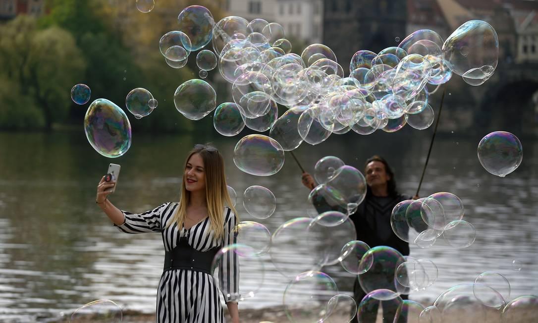 Uma turista faz selfie enquanto um artista faz bolhas de sabão na margem do rio Vltava, em Praga, República Checa Foto: MICHAL CIZEK / AFP