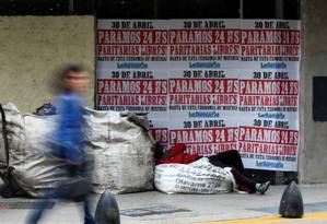 Sem-teto dorme diante de uma casa de câmbio em Buenos Aires, com pôsteres na parede anunciando uma greve geral em 30 de abril em Buenos Aires: economia pressiona Macri Foto: AGUSTIN MARCARIAN/REUTERS/25-04-2019