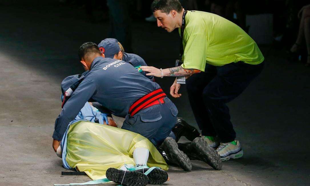 Tales Cotta sendo atendido na passarela Foto: Alexandre Schneider / Getty Images