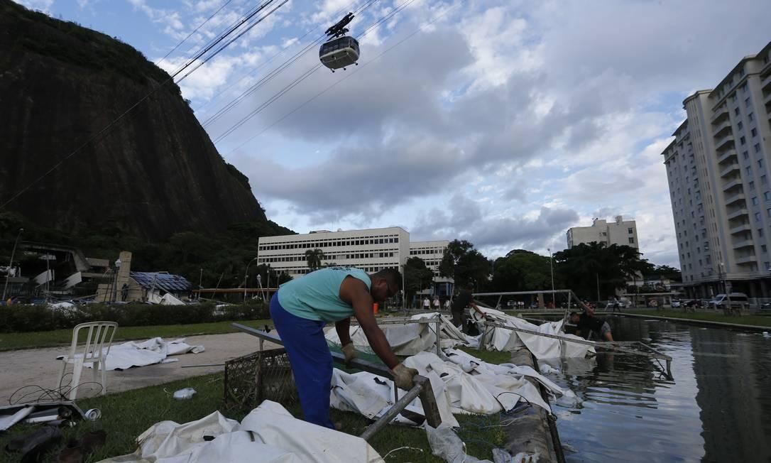 Operário recolhe parte da estrutura das tendas que foram arrancadas pelo vento forte na noite deste domingo Foto: Pablo Jacob / Agência O Globo