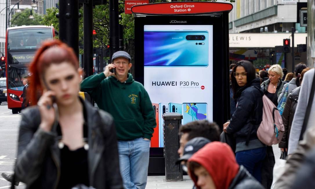 Pedestres usam seus celulares perto de um anúncio da Huawei em um ponto de ônibus no centro de Londres. O secretário de Relações Exteriores britânico, Jeremy Hunt, pediu cautela sobre o papel da chinesa Huawei no Reino Unido, dizendo que o governo deveria pensar cuidadosamente antes de abrir portas para o gigante da tecnologia para desenvolver redes móveis 5G no país Foto: TOLGA AKMEN / AFP