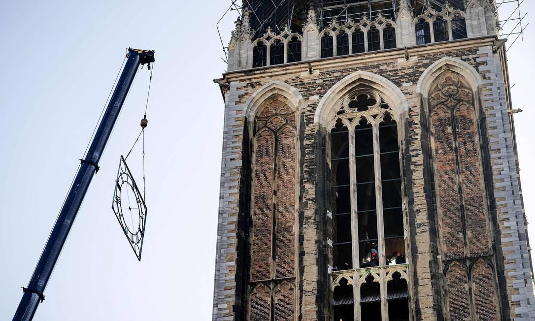 Guindaste remove uma moldura de relógio da Torre Dom, em Utrecht, na Holanda, antes de um longo período de restauração do monumento Foto: ROBIN VAN LONKHUIJSEN / AFP