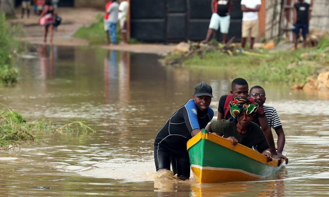 Um homem transporta moradores em barco por uma estrada inundada após o ciclone Kenneth em Pemba, no Norte de Moçambique Foto: MIKE HUTCHINGS / REUTERS
