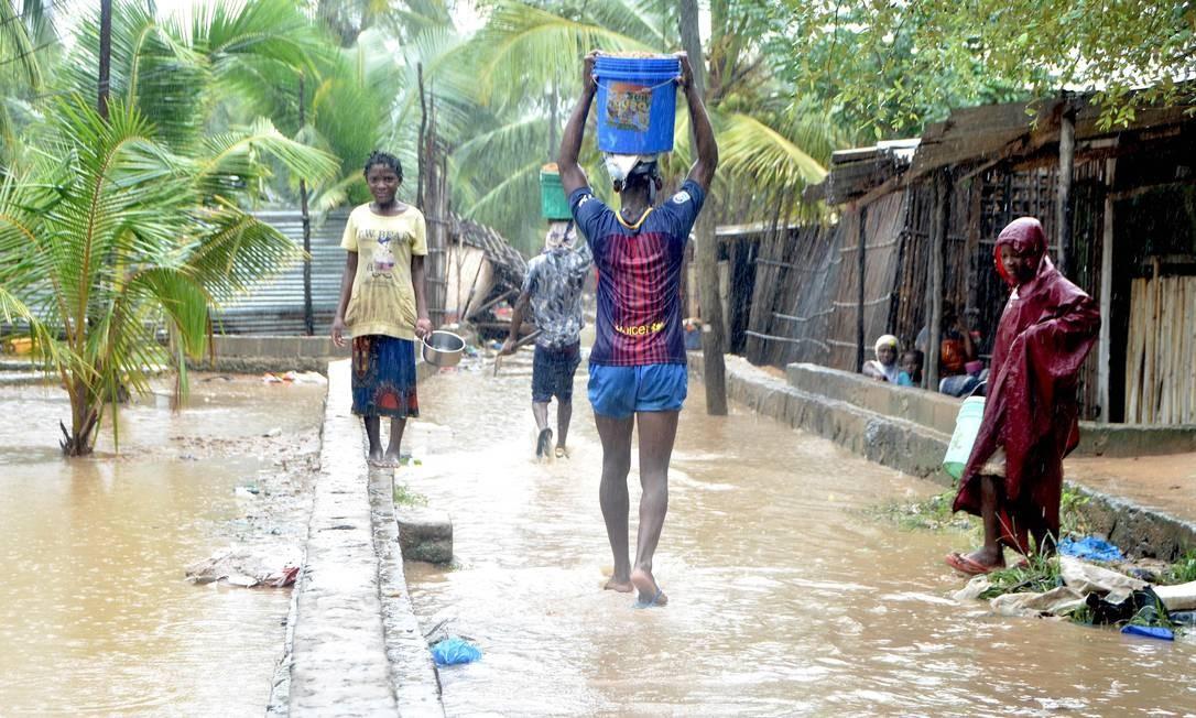 Moradores caminham pelas ruas inundadas do distrito de Paquite, em Pemba. O ciclone Kenneth atingiu o Norte de Moçambique no último domingo, matando 38 pessoas e destruindo milhares de casas, apenas cinco semanas após o ciclone Idai atingir a cidade de Beira, no Sul do país Foto: EMIDIO JOZINE / AFP