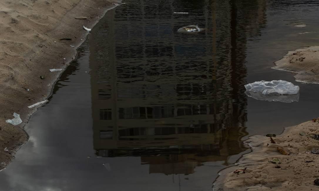 Reflexos de um problema sem solução: lixo no meio da língua negra Foto: Brenno Carvalho / Agência O Globo