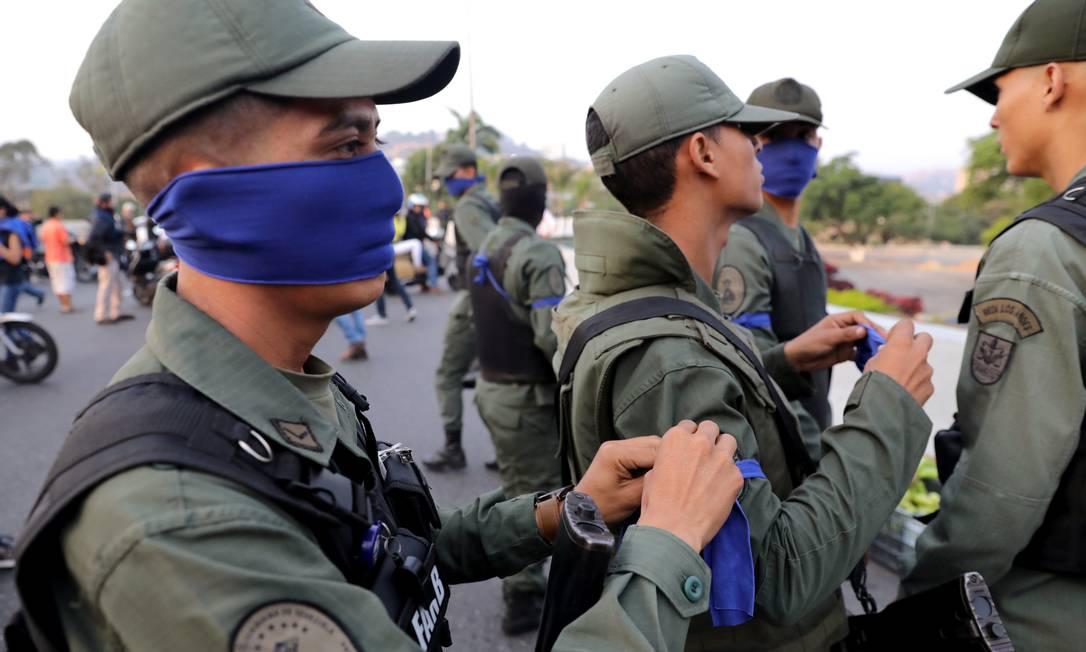 Soldados que desertaram em apoio à oposição venezuelana usam adornos azuis para cobrir os rostos, perto de base militar em Caracas. Governo chavista ressalvou que não há mobilização nas instalações militares do país Foto: STRINGER / REUTERS