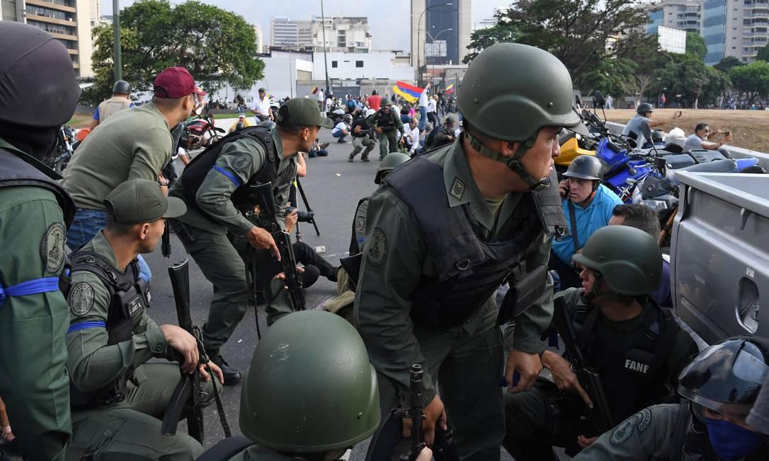 Membros da Guarda Nacional Bolivariana que se juntaram à oposição se posicionam em front perto da base de La Carlota, em Caracas. Governo disse que forças militares estão sob controle Foto: YURI CORTEZ / AFP