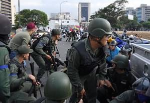 Membros da Guarda Nacional Bolivariana que se juntaram à oposição se posicionam perto da base de La Carlota, em Caracas. Governo disse que forças militares estão sob controle Foto: YURI CORTEZ / AFP