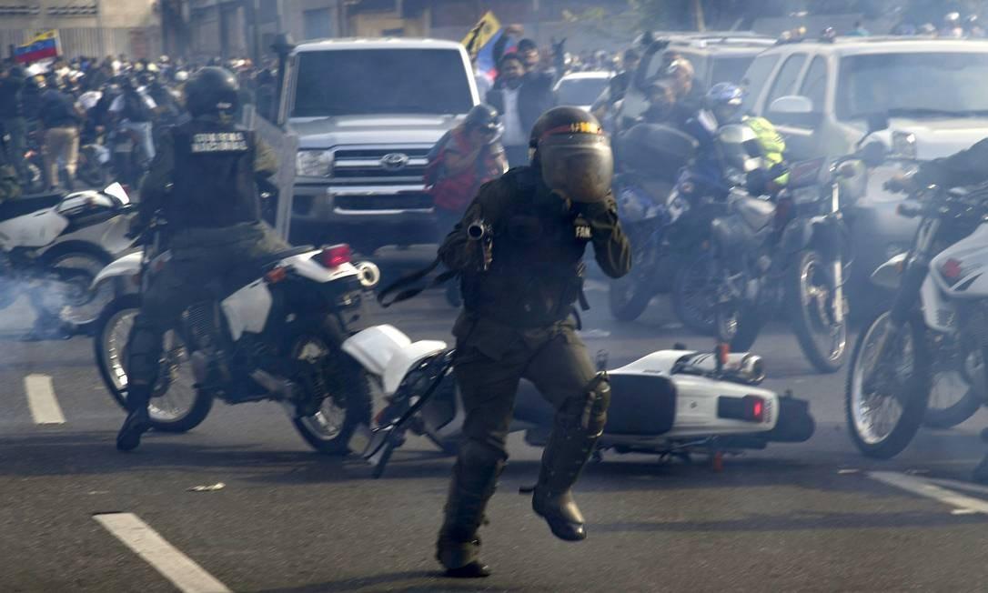 Membros da Guarda Nacional Bolivariana, leais ao presidente venezuelano Nicolas Maduro, correm sob uma nuvem de gás lacrimogêneo depois de serem repelidos por guardas que apoiam o líder da oposição venezuelana Juan Guaido ao chegar para dispersar os manifestantes em frente à base militar de La Carlota Foto: YURI CORTEZ / AFP