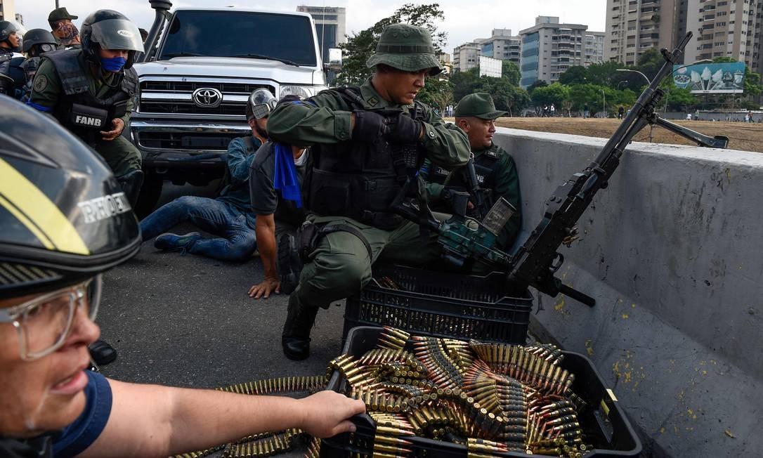 Membros da Guarda Nacional Bolivariana que se juntaram ao líder da oposição venezuelana Juan Guaidó se posicionam depois de repelir as forças leais ao presidente Nicolas Maduro, que chegou para dispersar uma manifestação em frente à base militar de La Carlota Foto: FEDERICO PARRA / AFP