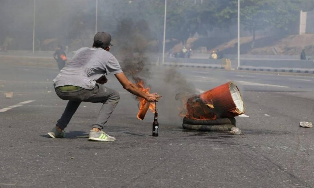 Um militante pró-Guaidó prepara um coquetel Molotov para enfrentar militares que defendem a ditadura de Maduro. Foto: Anadolu Agency / Getty Images