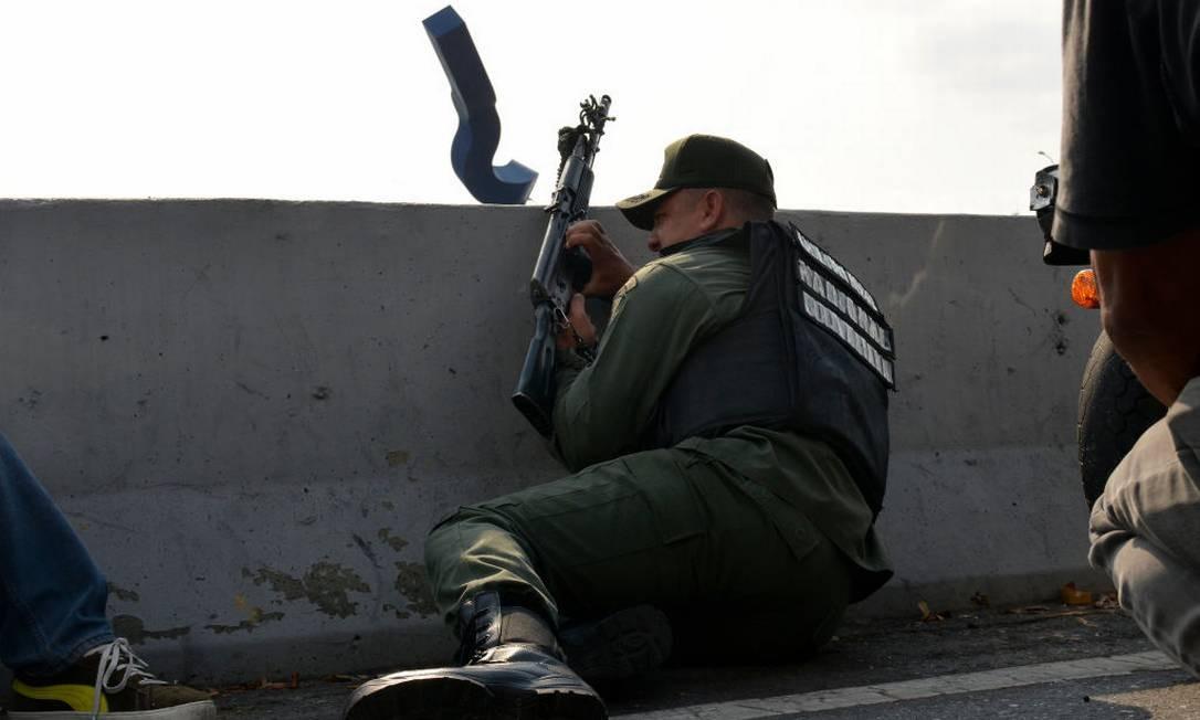 Um soldado pró-Guaidó se protege em uma barreira de concreto nas proximidades da base aérea de La Carlota, no bairro de de Altamira, em Caracas. Foto: Getty Images / Getty Images