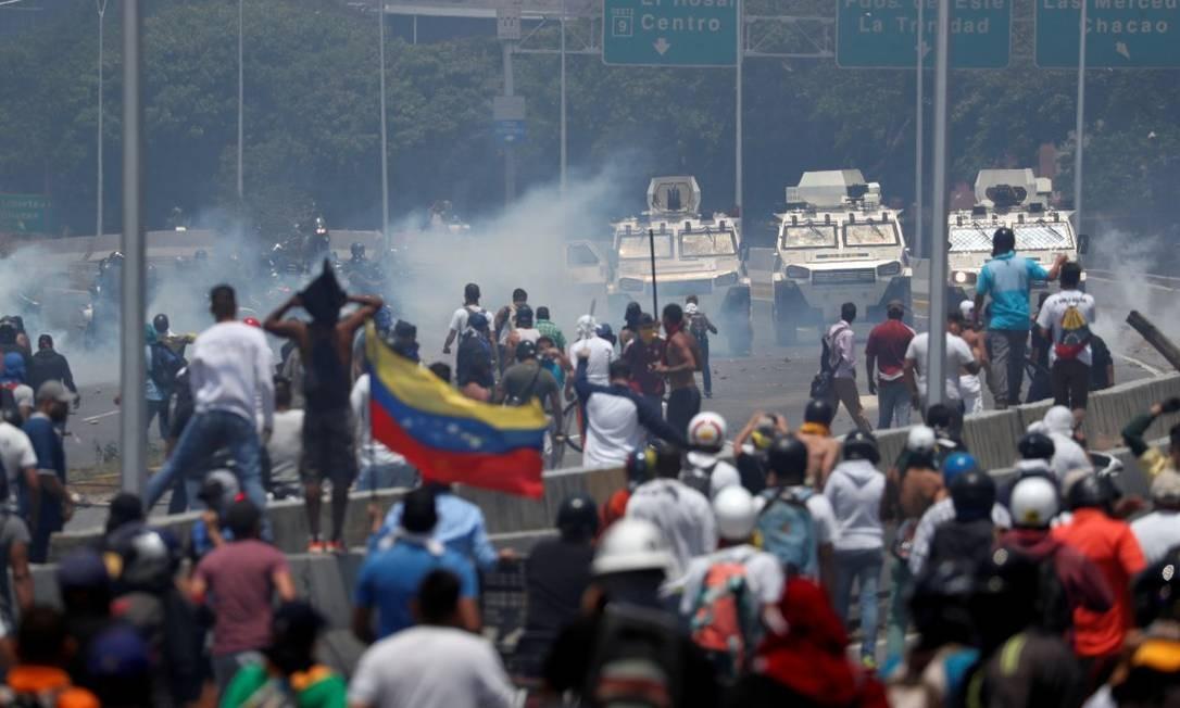 Manifestantes enfrentam veículos militares perto da base La Carlota em Caracas Foto: CARLOS GARCIA RAWLINS / REUTERS 30-4-19