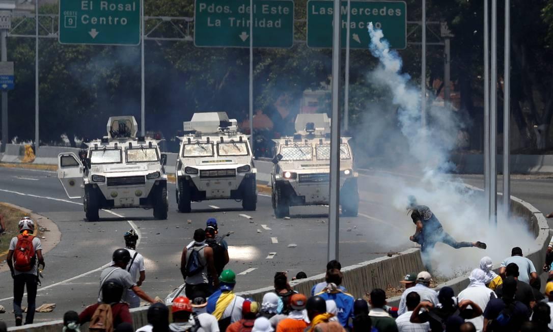 Manifestantes em apoio a Juan Guaidó entram em confronto com miltares, que respondem avançando contra protesto Foto: CARLOS GARCIA RAWLINS / REUTERS