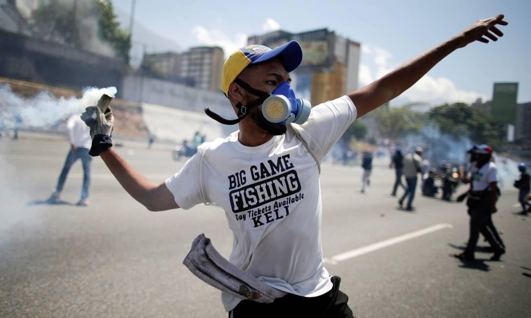 Opositor lança de volta bomba de gás lacrimogêneo; violência tomou conta das ruas de Altamira, na capital venezuelana Foto: UESLEI MARCELINO / REUTERS