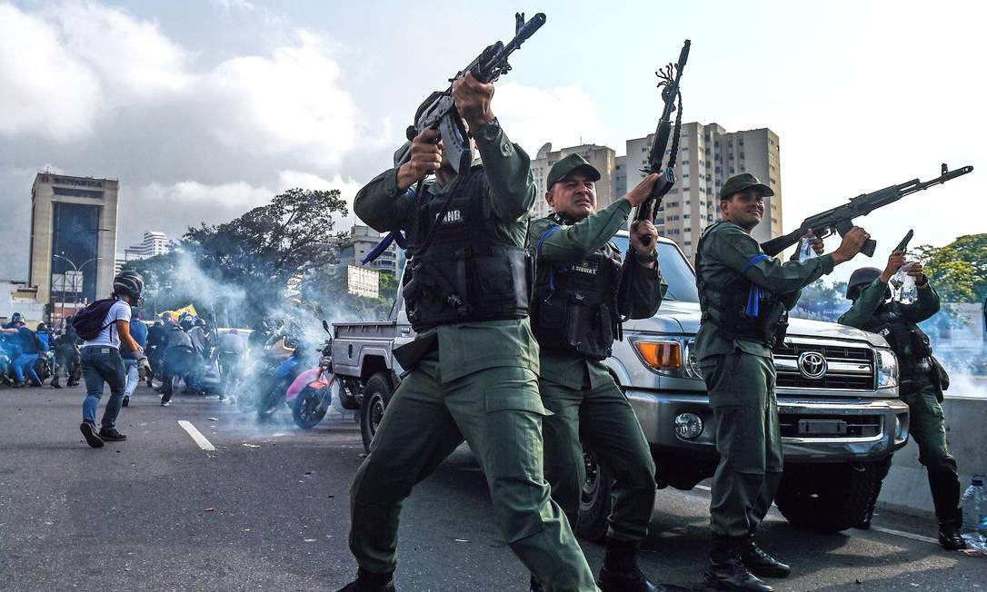 Membros da Guarda Nacional Bolivariana que se uniram a Juan Guaidó disparam para dispersar manifestantes perto de La Carlota; forças militares são importantes aliadas de Maduro na Venezuela Foto: FEDERICO PARRA / AFP