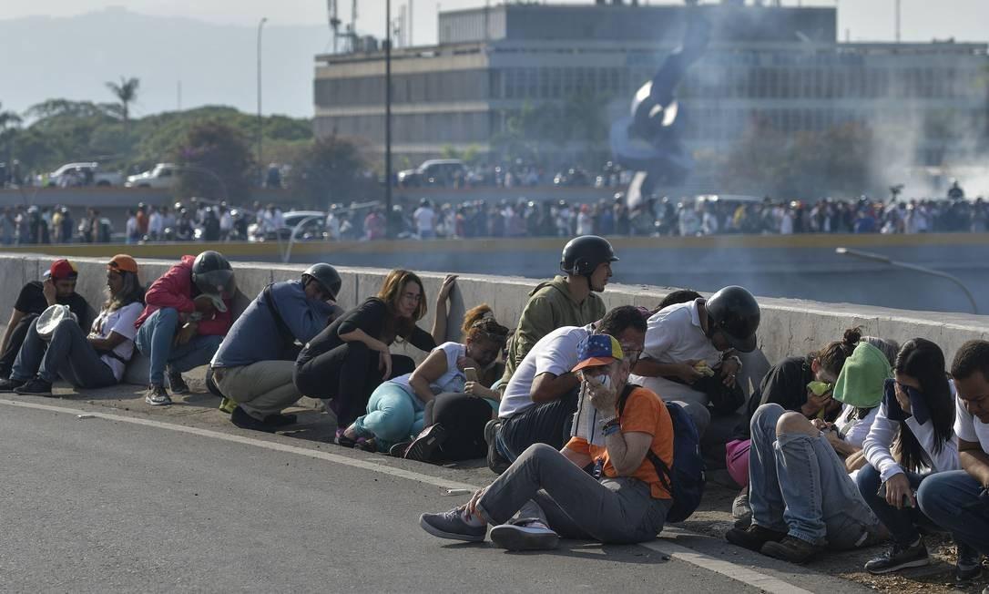 Apoiadores de Guaidó se protegem atrás de mureta das forças de Maduro em Caracas Foto: MATIAS DELACROIX / AFP
