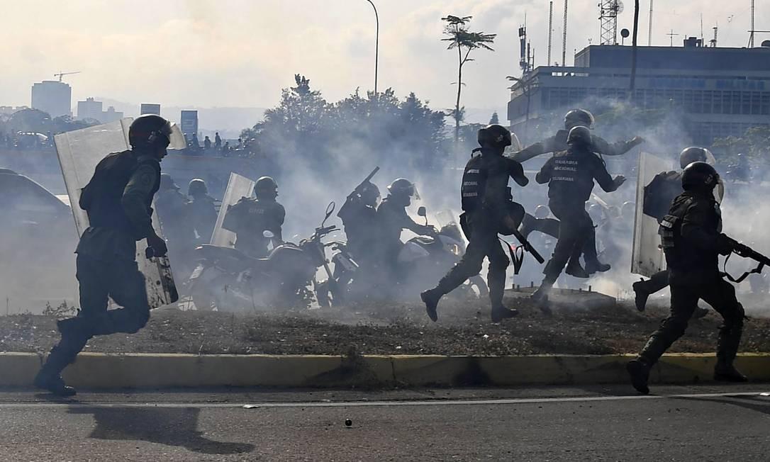 Membros da Guarda Nacional Bolivariana correm em meio à nuvem de gás lacrimogêneo durante repressão a protestos em Caracas Foto: YURI CORTEZ / AFP
