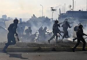Membros da Guarda Nacional Bolivariana correm sob nuvem de gás lacrimogêneo durante repressão a protestos massivos em Caracas Foto: YURI CORTEZ / AFP