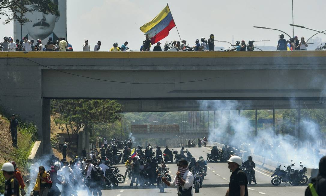 Manifestantes correm pelas ruas de Caracas perto da base áerea La Carlota, onde Guaidó reuniu militares a seu favor; Venezuela vive dia de alta tensão política Foto: MATIAS DELACROIX / AFP