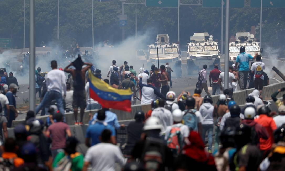 Opposition demonstrators face military vehicles near the Generalisimo Francisco de Miranda Airbase