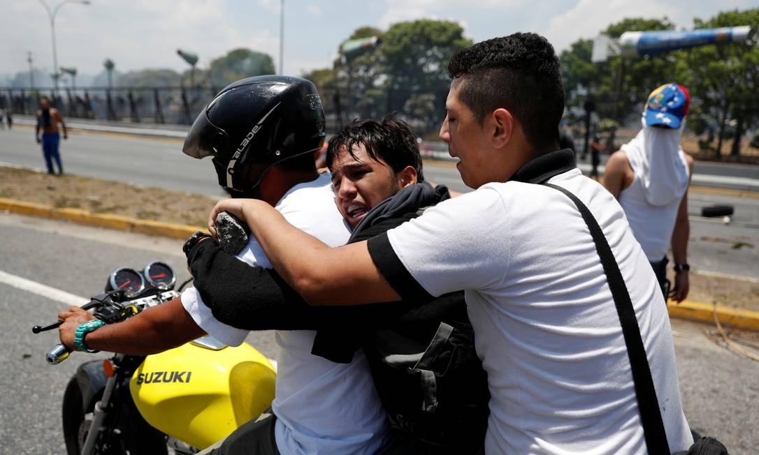 Manifestantes ajudam homem ferido durante dia de protestos na Venezuela Foto: CARLOS GARCIA RAWLINS / REUTERS