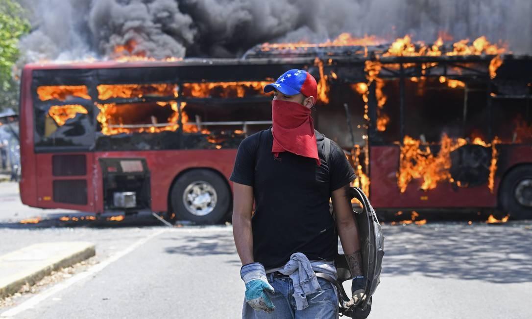 """Ônibus é incendiado durante confrontos de manifestantes com soldados leais ao presidente venezuelano, Nicolás Maduro, depois que parte dos militares se uniu ao líder da oposição Juan Guaidó, nos arredores da base militar de Carlota, em 30 de abril de 2019. Guaidó — acusado pelo governo de tentar um golpe nesta terça-feira — disse que """"não há como voltar atrás"""" em sua tentativa de expulsar Maduro do poder Foto: FEDERICO PARRA / AFP"""