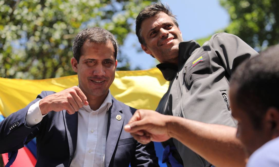 O líder da oposição venezuelana, Juan Guaidó, que mais de 50 países reconheceram como o legítimo governante interino do país, entre eles Brasil e EUA, cumprimenta um apoiador enquanto o colega Leopoldo Lopez, observa o público de manifestantes, em Caracas, nesta terça-feira Foto: STRINGER / REUTERS