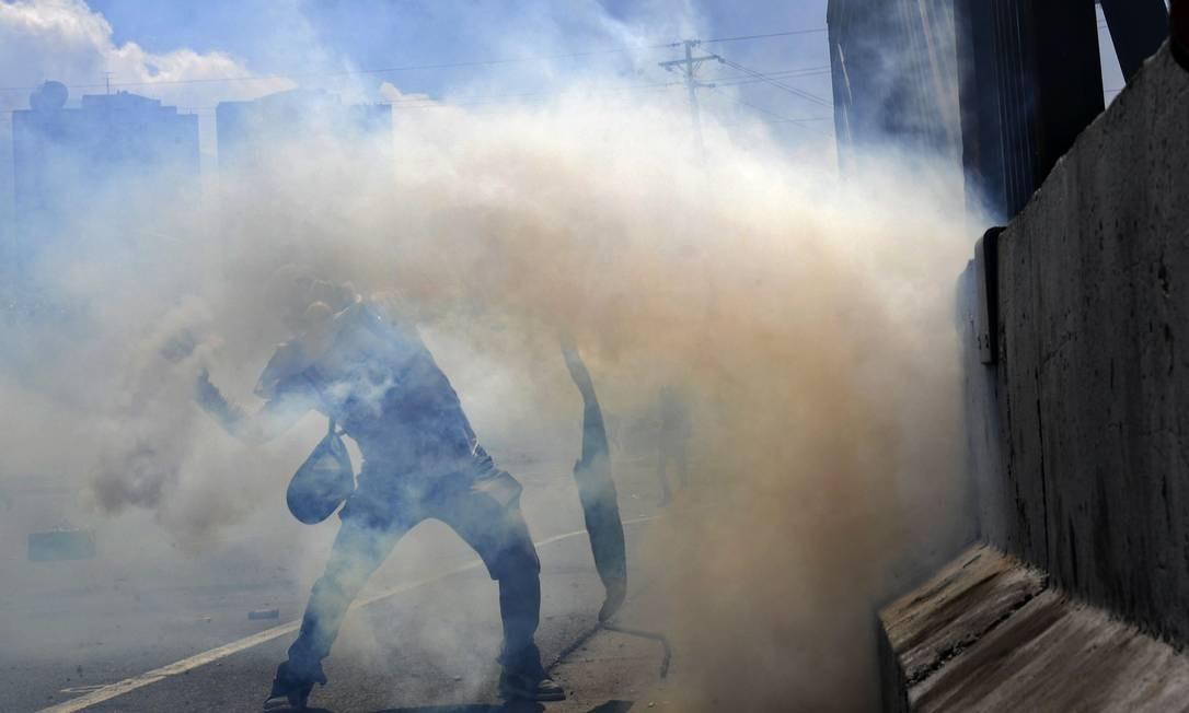 """Manifestantes usam máscaras e tecidos para se protegerem do gás e revidam os soldados com pedras. Uma parte dos militares uniu-se à tentativa de derrubar o governo de Maduro. Em vídeo postado às 5h47 locais (6h47 no Brasil), Guaidó apareceu cercado de militares, afirmando que """"valentes soldados acudiram ao nosso chamado"""" e conclamando a população a ir às ruas Foto: YURI CORTEZ / AFP"""