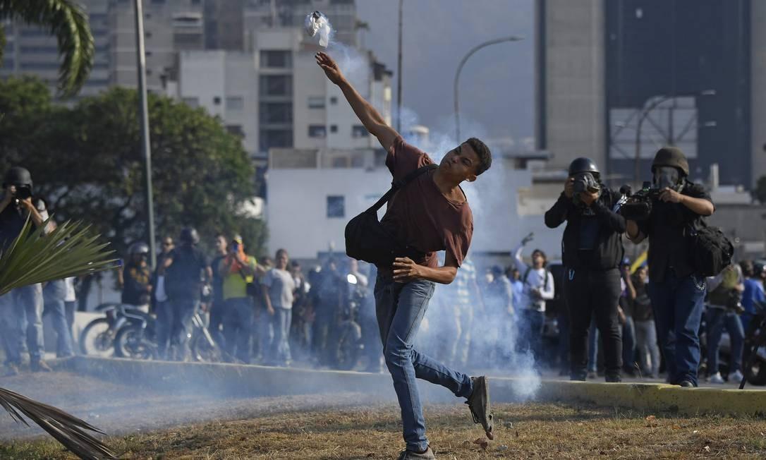 """Manifestantes da oposição entram em conflito com soldados leais a Maduro. O que a oposiçao chama de """"ação cívico militar"""", o governo define como """"uma ação terrorista e golpista"""" Foto: FEDERICO PARRA / AFP"""