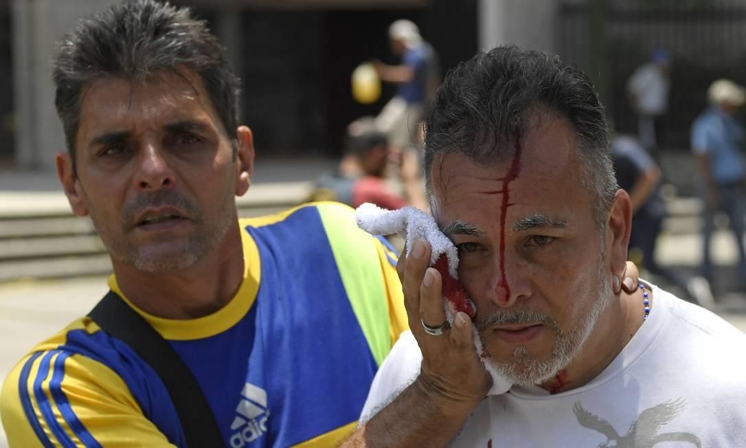 Um manifestante é ferido durante os confrontos em Caracas. Militares reagiram aos protestos organizados por Guaidó Foto: FEDERICO PARRA / AFP