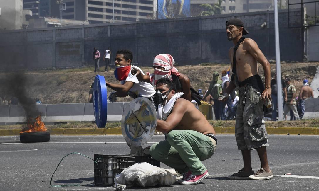 """Manifestantes da oposição se protegem com tampas de plástico das investidas das tropas do governo. Guaidó, que se autoproclamou presidente interino em 23 de janeiro, afirmou que não """"tem mais volta"""" em sua campanha para depor Maduro do poder. O ministro da Defesa da Venezuela, Vladimir Padrino López, denunciou pela TV uma tentativa de golpe de Estado """"insignificante"""" na Venezuela , que segundo ele foi """"parcialmente derrotada"""" Foto: YURI CORTEZ / AFP"""