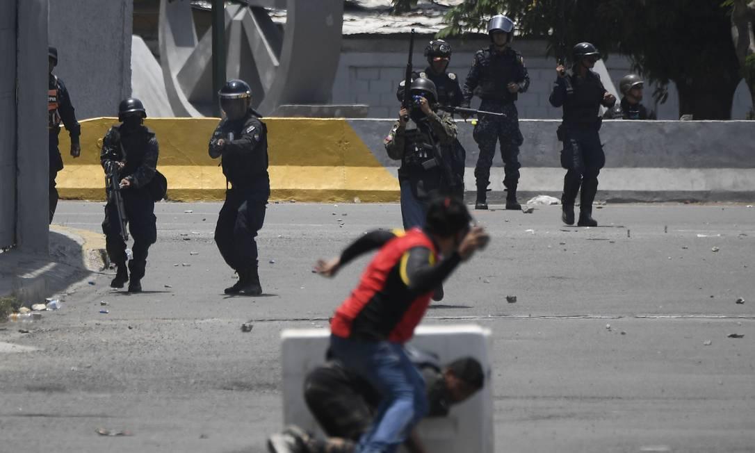 Apoiadores de Guaidó revidam os soldados com pedras, enquanto alguns tentam se proteger. Conflitos ocorrem nos arredores da base militar La Carlota, em Caracas. Blindados atropelaram manifestantes Foto: FEDERICO PARRA / AFP