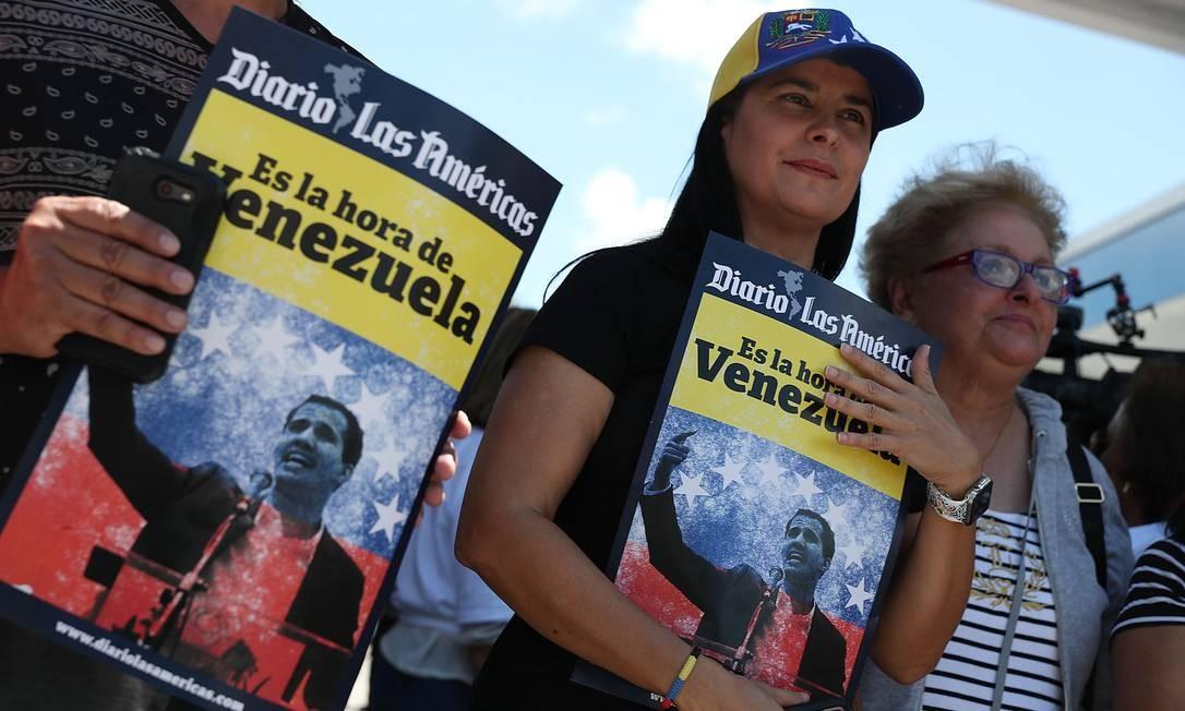 """Na Flórida, Janine Paz e outros venezuelanos mostram seu apoio a Guaidó, durante uma manifestação em frente ao restaurante venezuelano El Arepazo Doral. O ministro de Defesa da Venezuela, Vladimir Padrinho, criticou """"a oposição golpista e selvagem"""" Foto: JOE RAEDLE / AFP"""