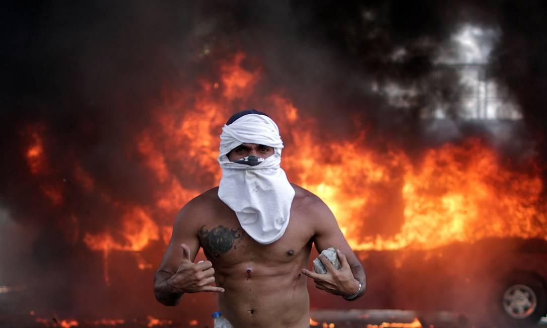 Um ônibus queima atrás de um dos manifestantes que aderiu aos protestos contra o regime de Nicolás Maduro. Foto: UESLEI MARCELINO / REUTERS
