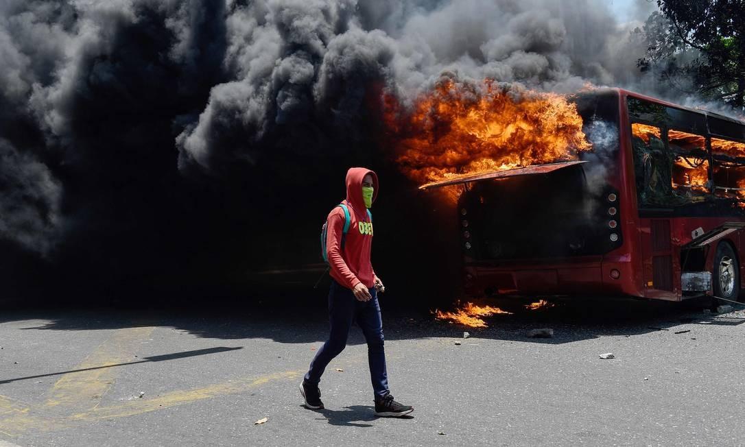 Um ônibus queima atrás de um dos manifestantes que aderiu aos protestos contra o regime de Nicolás Maduro. Foto: FEDERICO PARRA / AFP