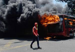 Manifestante opositor passa por ônibus em chamas em Caracas Foto: FEDERICO PARRA / AFP