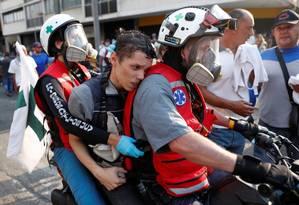 Manifestante ferido é levado por paramédicos em Caracas Foto: CARLOS GARCIA RAWLINS / REUTERS