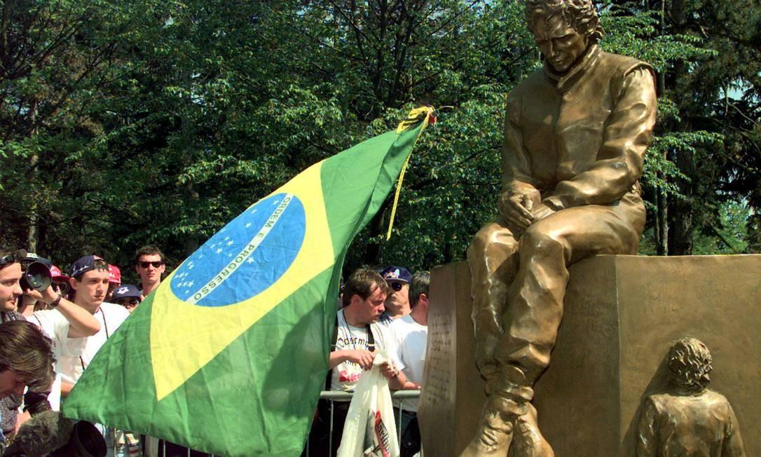 Fãs carregando uma bandeira do Brasil se reúnem para ver a inauguração de uma estátua do ex-piloto de Fórmula 1 brasileiro Ayrton Senna, no local do autódromo de Imola, onde Senna foi morto há três anos durante o Grande Prêmio de San Marino, em Imola, Itália 25 de abril de 1997 Foto: Paul Hanna / REUTERS