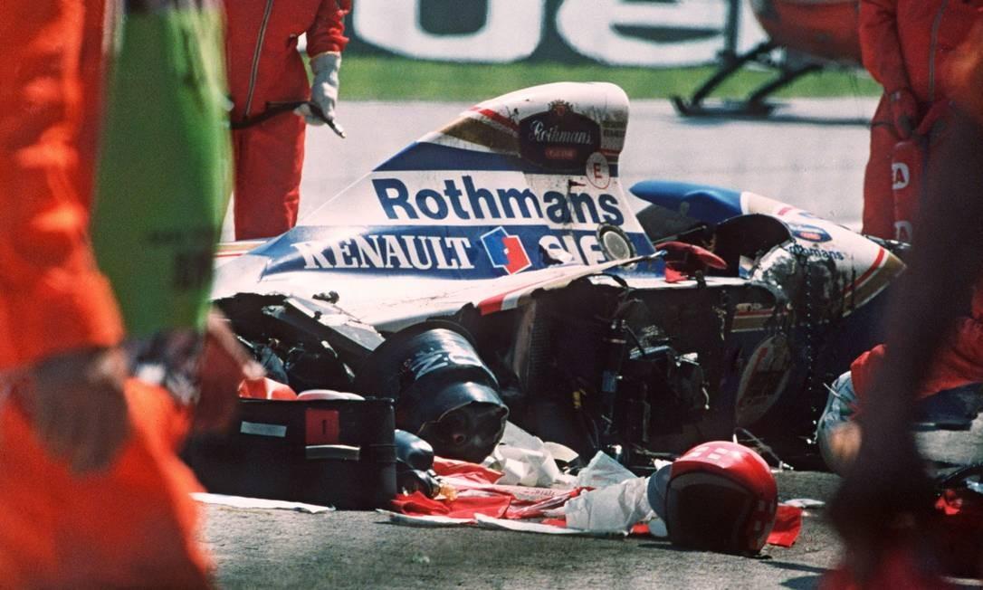 Homens da segurança segurança se aproximam do carro acidentado de Ayrton Senna na pista de Ímola Foto: JEAN-LOUP GAUTREAU / AFP