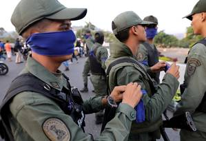 Militares venezuelanos colocam faixas azuis em sinal de apoio a Guaidó em Caracas Foto: STRINGER / REUTERS