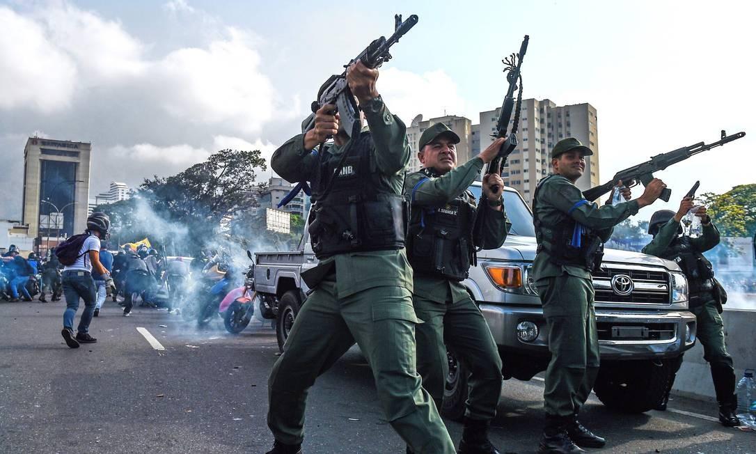 Membros da Guarda Nacional Bolivariana que se uniram ao opositor Juan Guaidó atiram durante dia de confrontos em Caracas Foto: FEDERICO PARRA / AFP