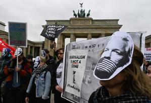 Manifestantes usam máscaras de Julian Assange durante ato de apoio a fundador do Wikileaks, em Berlim Foto: JOHN MACDOUGALL 02-02-2019 / AFP