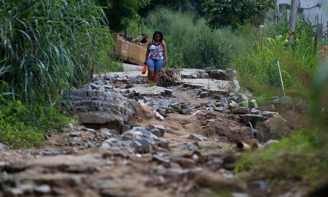 Mulher caminha em rua totalmente destruída no Condominio Figueiras do Itanhangá, onde desabaram dois prédios Foto: Fabiano Rocha / Agência O Globo