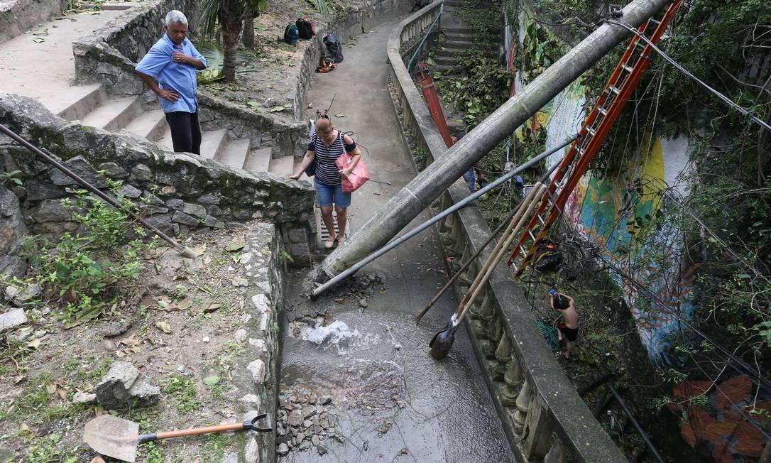 Moradores passam no meio da destruição deixada pelo vendaval na Travessa Cassiano, em Santa Teresa Foto: Pedro Teixeira / Agência O Globo