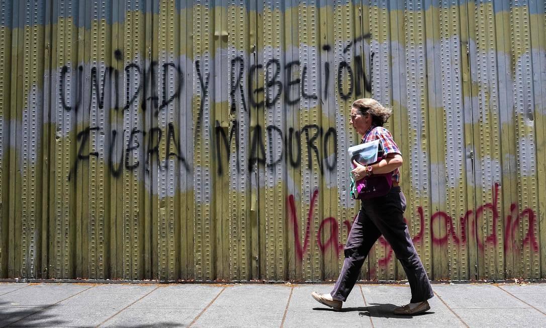 Mulher passa por um grafite com a inscrição 'unidade e rebelião, fora Maduro' em Caracas: autoridades brasileiras rejeitam intervenção Foto: / FEDERICO PARRA/AFP