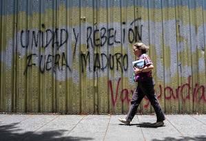 Mulher passa por um grafite com a inscrição 'unidade e rebelião, fora Maduro' em Caracas: autoridades brasileiras rejeitam intervenção Foto: FEDERICO PARRA/AFP