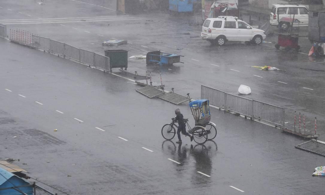 Um morador indiano puxa seu riquixá de ciclismo em uma rua após passagem do ciclone Fani, em Puri, no estado indiano de Odisha. Duas pessoas morreram depois que o ciclone atingiu o leste da Índia, segundo as autoridades. O Fani é um dos mais fortes ciclones a sair do Oceano Índico em anos, com ventos que sopram a velocidades de até 200 quilômetros por hora Foto: DIBYANGSHU SARKAR / AFP