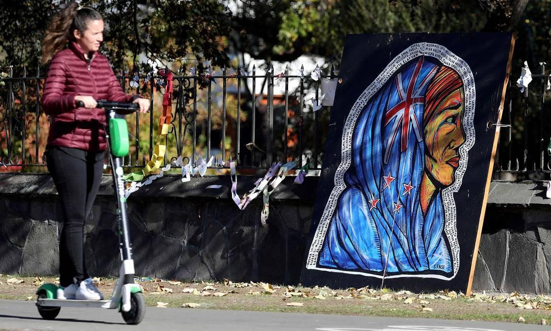 Uma mulher passa por arte que representa uma mulher Mauri com lenço na cabeça, projetada com a bandeira nacional da Nova Zelândia, do lado de fora do Jardim Botânico em Christchurch. O número de mortos nos ataques da mesquita de Christchurch subiu para 51 Foto: SANKA VIDANAGAMA / AFP